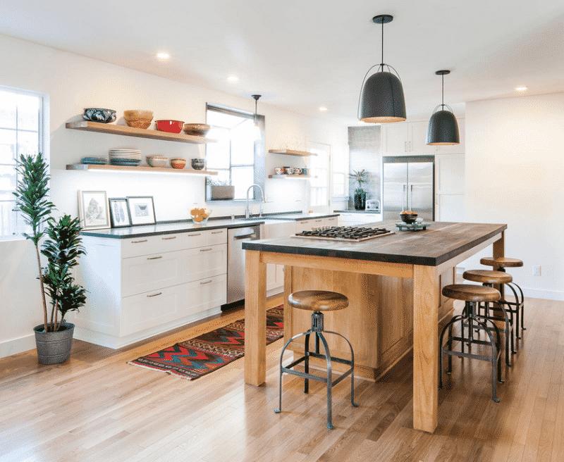 îlot de cuisine en bois qui contraste avec des meubles blancs