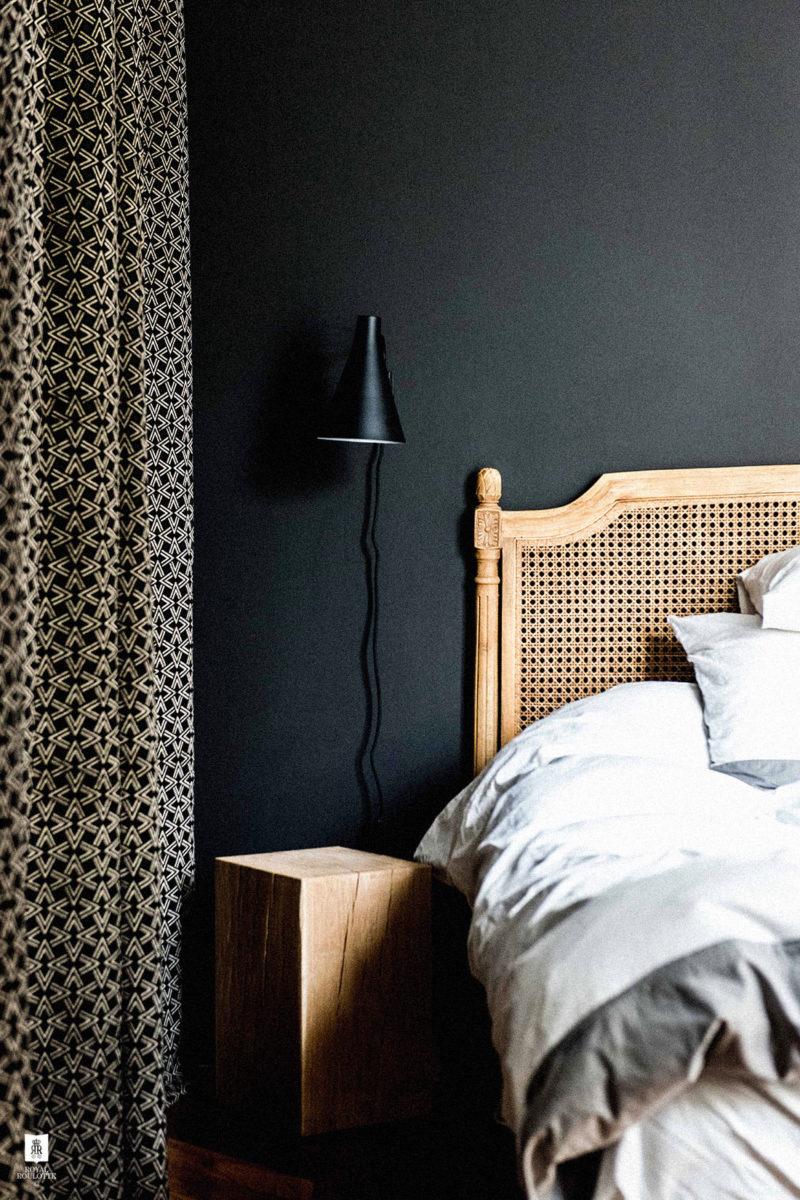 On adore cette combinaison de mur noir avec une tête de lit cannage