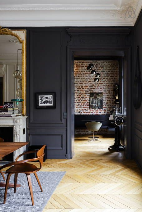 Parquet massif, mur en briques et couleur noire sur les murs pour une décoration chic